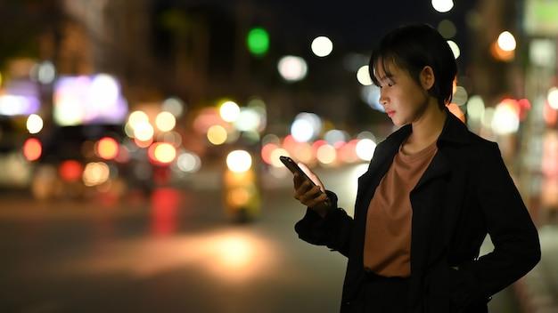 Молодая женщина ждет своего частного такси, используя мобильное приложение для транспорта