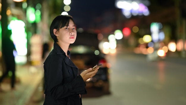 携帯電話で交通機関アプリを使用している間、若い女性がプライベートタクシーを待つ