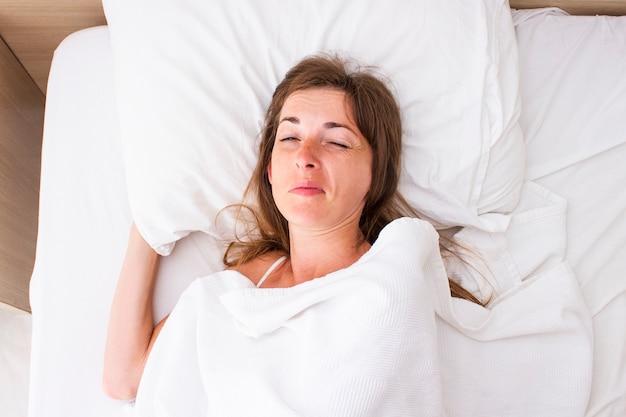 Молодая женщина просыпается в постели. понятие бессонницы, снов, снотворного, хорошего сна, хорошего секса. плоская планировка, вид сверху