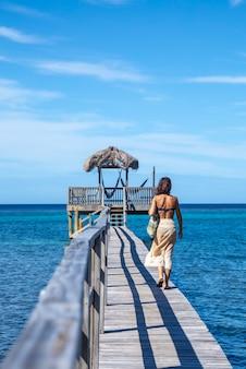 ロアタン島のサンディベイのビーチに沿って歩く若い女性。ホンジュラス