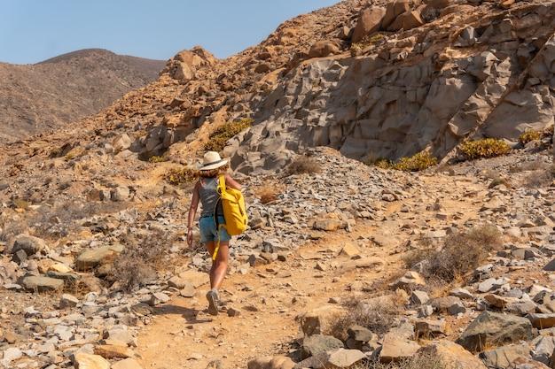 카나리아 제도 푸에르테벤투라 섬의 서쪽 해안인 mirador de la peñitas를 향해 협곡 길을 걷고 있는 젊은 여성. 스페인