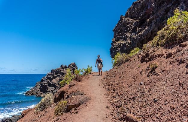 カナリア諸島のラプラマ島の東にあるノガレスのビーチに夏の道を歩く若い女性。スペイン