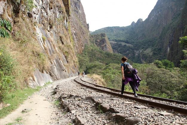 트레킹에서 기차를 따라 걷는 젊은 여성이 aguas calientes에 도착합니다.