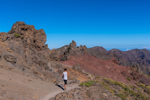 Молодая женщина гуляет на вершине вулкана кальдера-де-табуриенте недалеко от роке-де-лос-мучачос одним летним днем, ла-пальма, канарские острова. испания