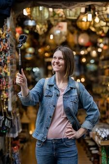 Молодая женщина, идущая счастливо на улице. кавказская туристическая девушка, посетив старый город.