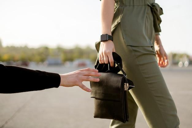 Молодая женщина, идущая по городской улице, и грабитель пытаются украсть ее сумку, понятие преступности и насилия