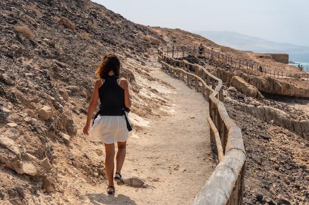 Молодая женщина идет по тропе в куэвас-де-ажуи, пахара, западное побережье острова фуэртевентура, канарские острова. испания