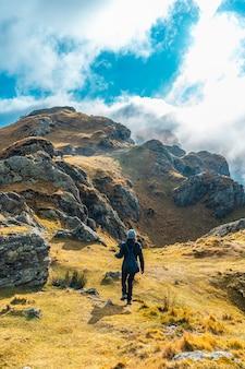 Молодая женщина гуляя на вершину горы aiako harria день облаков, гипускоа. страна басков