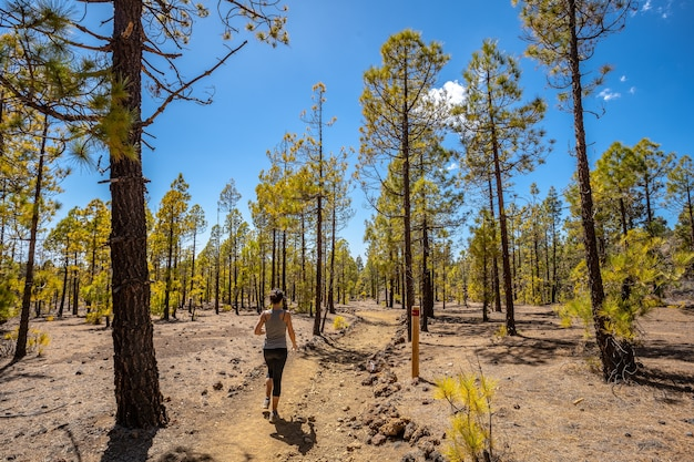 テイデ山の森をトレッキングで歩く若い女性