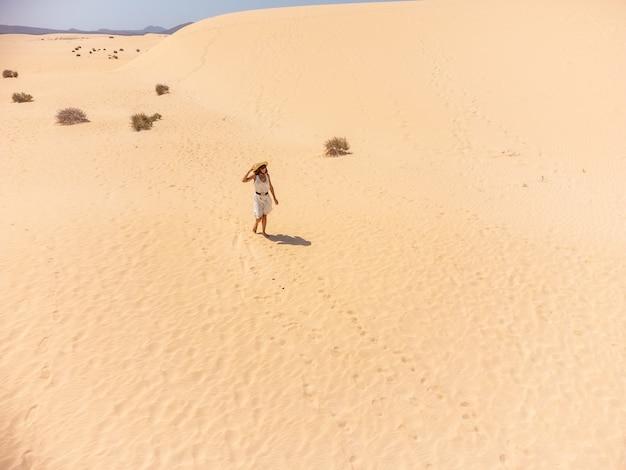 카나리아 제도 푸에르테벤투라에 있는 코랄레호 자연 공원의 모래 언덕을 걷고 있는 젊은 여성. 스페인