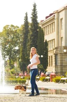 Молодая женщина гуляет с собакой породы бигль на поводке возле фонтана в парке