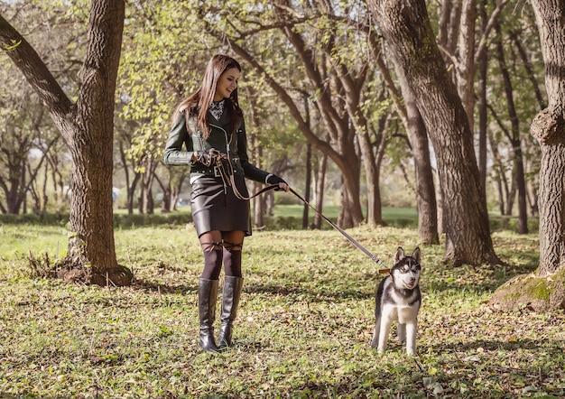 Молодая женщина гуляет с собакой в парке в солнечный октябрьский день