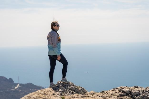 若い女性が海の岩だらけの海岸に沿って歩きます。素晴らしい高さからの素晴らしい眺め。果てしなく続く海。