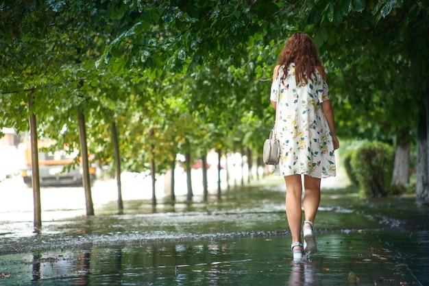 夏の雨の中、若い女性が通りを歩いています。