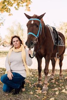 Молодая женщина гуляет в осеннем парке с коричневой лошадью, присевшей рядом
