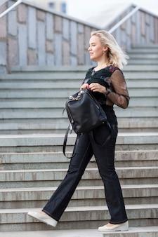 Молодая женщина поднимается по лестнице на улице. красивая блондинка в джинсах и с рюкзаком. вертикальный.