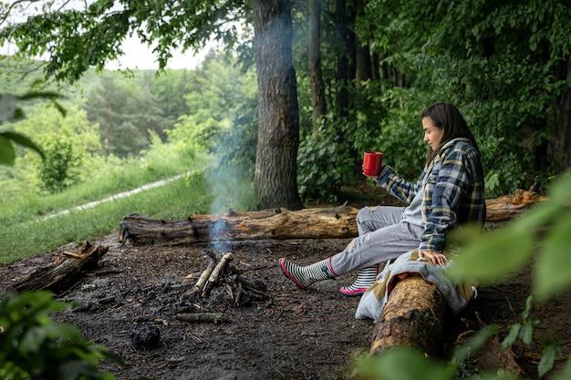 Молодая женщина греется у потухшего костра с чашкой согревающего напитка в лесу среди деревьев.