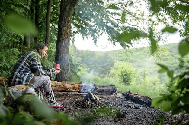 若い女性は、木々の間の森で温かい飲み物を飲みながら、消火の近くで暖まります。