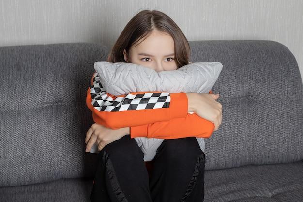 若い女性がテレビで怖い映画を見て、恐れて座って、枕を抱きしめます