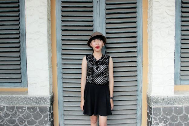 黒い帽子をかぶった黒いドレスを着た若い女性がドアの前に立っています