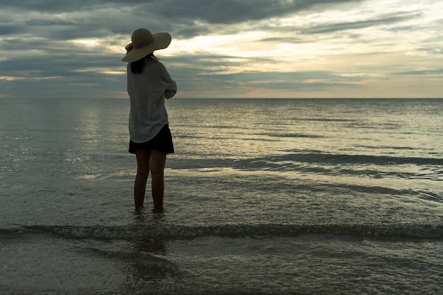 모자를 쓴 젊은 여성이 바닷가의 텅 빈 모래사장에 홀로 서 있습니다. 외로운 젊은 관광객들이 지평선을 바라보고 있습니다. 혼자, 여행의 개념