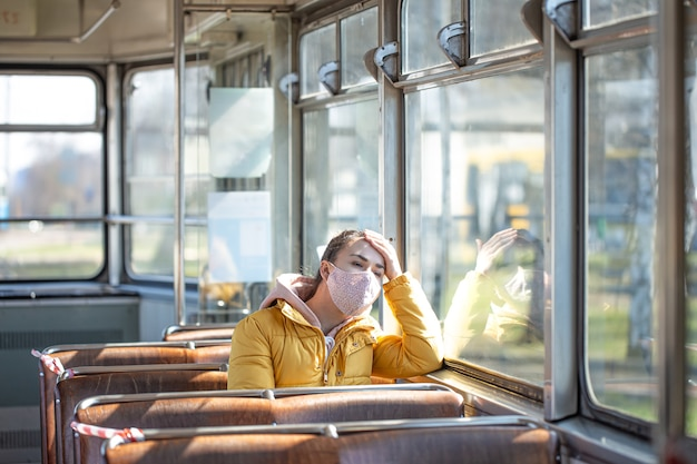 Молодая женщина в маске сидит одна в общественном транспорте во время пандемии коронавируса