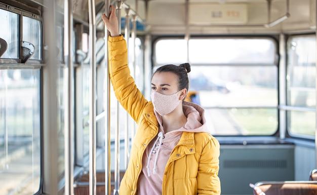 Молодая женщина в маске стоит одна в пустом общественном транспорте во время пандемии коронавируса