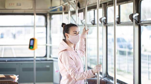 Молодая женщина в маске стоит одна в общественном транспорте во время вспышки пандемии коронавируса