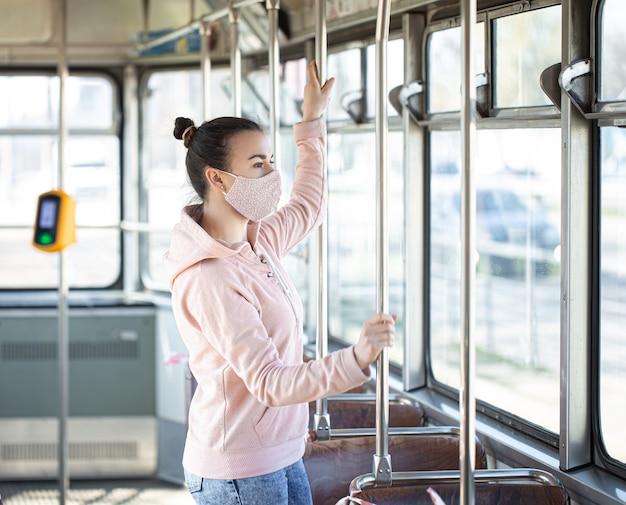 Молодая женщина в маске стоит одна в общественном транспорте во время пандемии коронавируса.