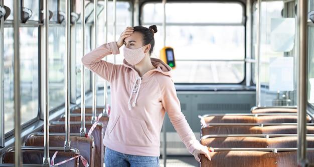 コロナウイルスのパンデミックの間、マスクをかぶった若い女性が公共交通機関で一人で立っています。