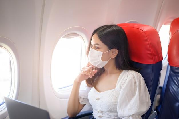Молодая женщина в маске использует ноутбук на борту, новое нормальное путешествие после концепции пандемии covid-19