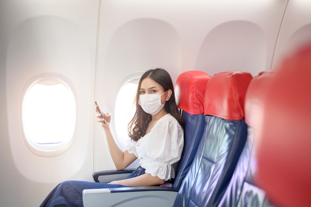 フェイスマスクを着た若い女性がスマートフォンを機内で使用している