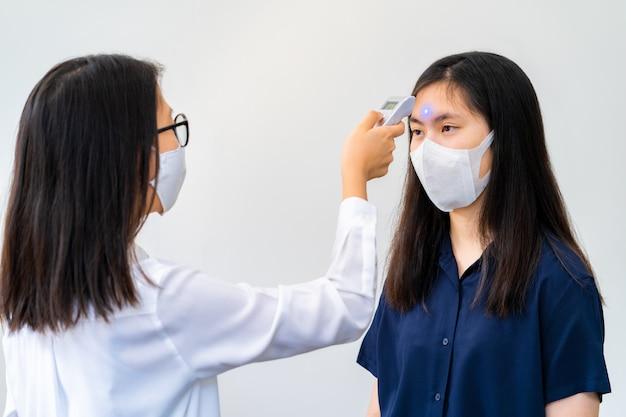 ハンドヘルド温度チェッカーを使用してフェイスマスクを着た若い女性がフェイスマスクを着た別の若い女性の体温をチェックする