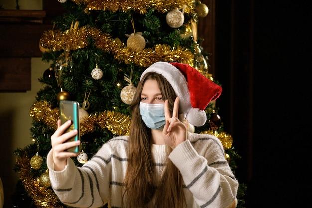 Молодая женщина в защитной маске и шляпе санта делает видеозвонок или видеочат дома на рождество