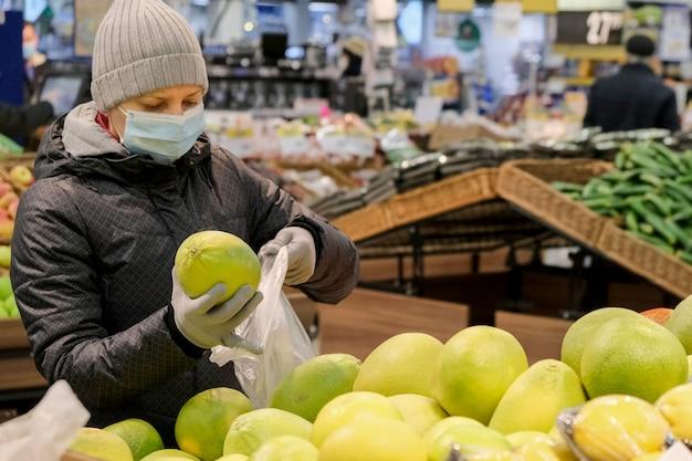 보호 장갑을 끼고있는 젊은 여성이 코로나 바이러스가 유행하는 동안 상점에서 음식을 구입합니다.