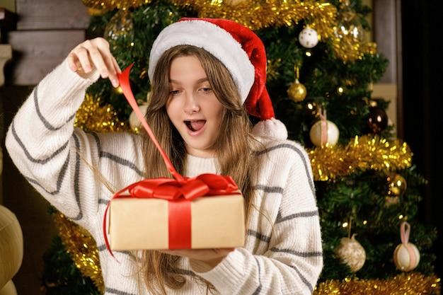 Молодая женщина в шляпе санта-клауса улыбается на камеру, открывая рождественский подарок