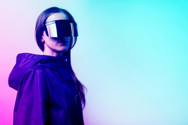 Vr 안경과 파란색 재킷을 입은 젊은 여성이 밝은 배경에 그라데이션을 추가했습니다.