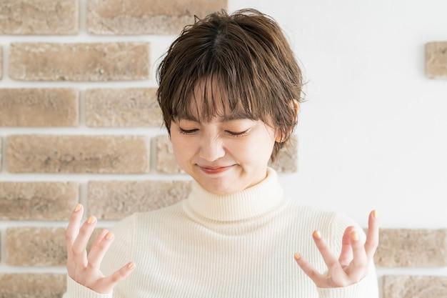 Молодая женщина, которая выражает свое разочарование руками и лицом