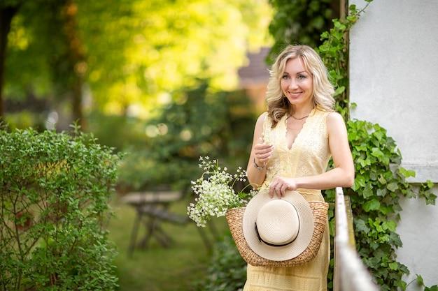 Молодая женщина с корзиной, букетом полевых цветов и шляпой стоит на фоне сада
