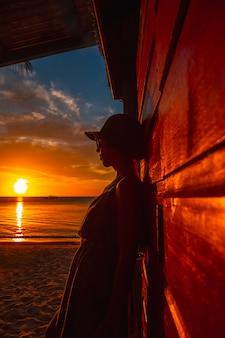 ロアタン島のカリブ海のウエストエンドサンセットで帽子をかぶった若い女性。ホンジュラス