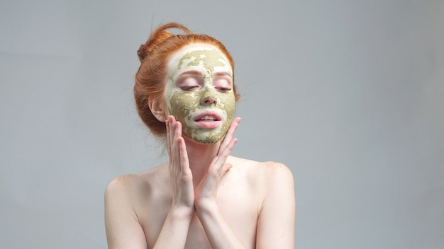 Молодая женщина с зеленой сухой грязевой маской на лице на изолированном фоне
