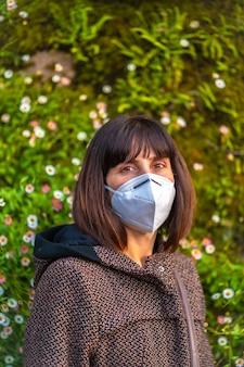 아름 다운 데이지 옆에 마스크와 젊은 여자. 통제되지 않은 covid-19 전염병의 첫 걸음