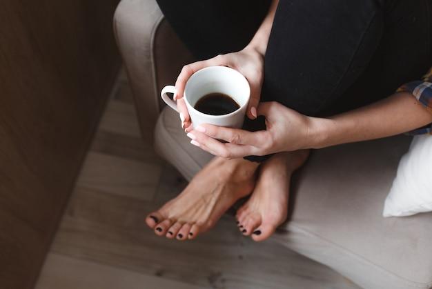 Молодая женщина с мобильным телефоном сидит в удобном кресле у окна дома и пьет чай. дизайн домашнего интерьера. фрилансер