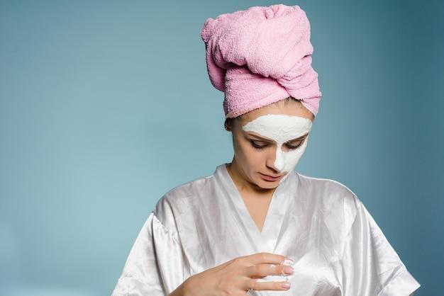ピンクのタオルを頭にかぶった若い女性が、顔の半分、スパに便利な保湿マスクを塗りました。
