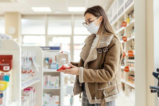 얼굴 보호 마스크와 안경을 쓴 젊은 여성이 약국에서 아기 용품을 구입합니다.