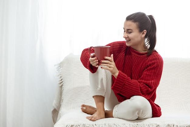 Молодая женщина с красной чашкой горячего напитка в уютном красном свитере отдыхает на диване у себя дома.