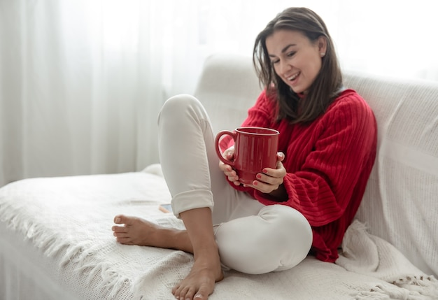 居心地の良い赤いセーターに赤いカップの温かい飲み物を持った若い女性が、自宅のコピースペースのソファで休んでいます。