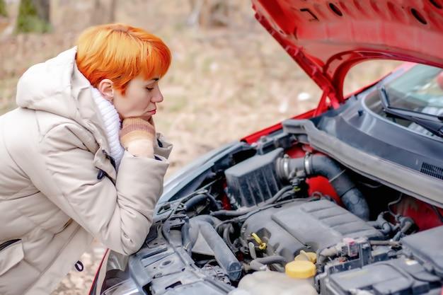 悲しい表情の若い女性が森の背景にある赤い車のエンジンルームの開いたボンネットを見て、壊れた車の隣の女の子