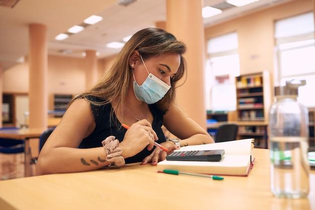 Молодая женщина с хирургической маской учится в библиотеке