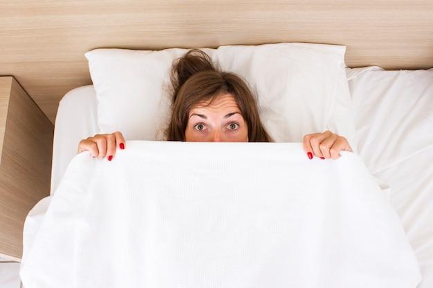 Молодая женщина с удивленным лицом лежит в постели. понятие бессонницы, снов, снотворного, хорошего сна, хорошего секса. плоская планировка, вид сверху